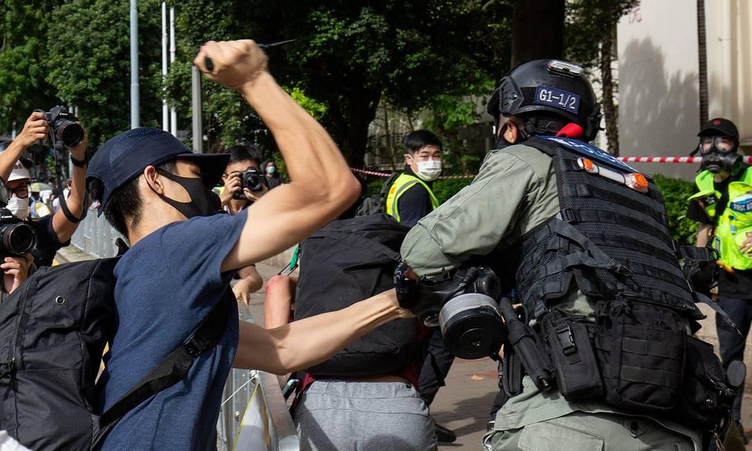 Manifestante usa um objeto afiado contra um policial que está tentando deter um homem durante protesto Foto: ALASTAIR PIKE / AFP