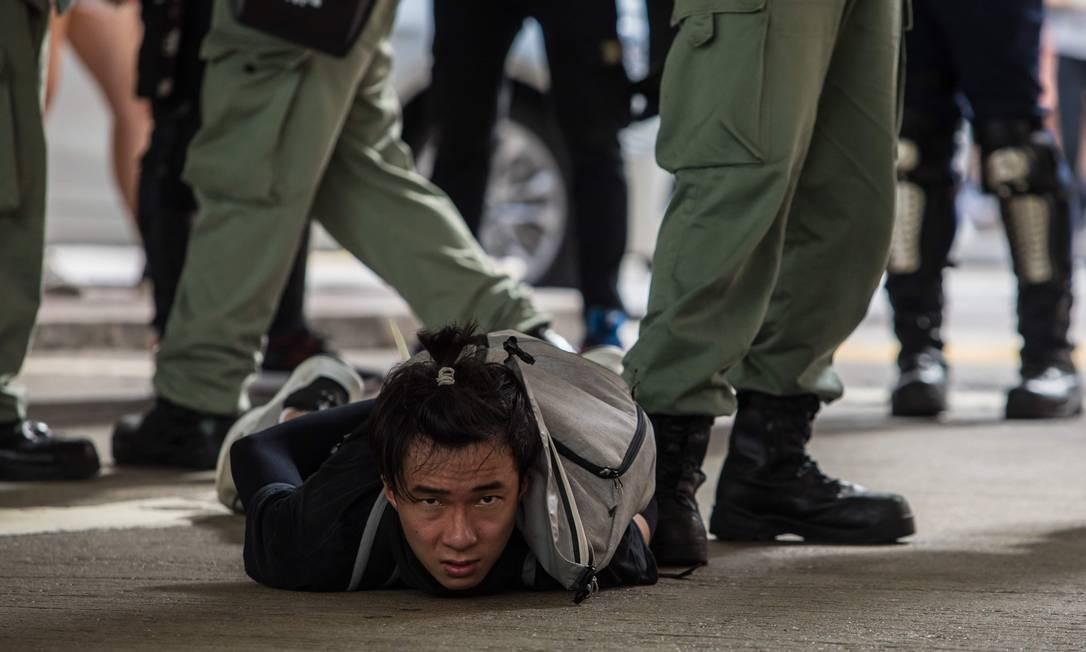 A polícia de choque detém um homem enquanto dispersa manifestantes Foto: DALE DE LA REY / AFP