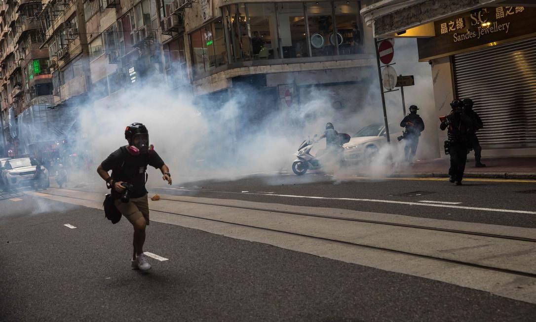 Manifestante foge de gás lacrimogêneo atirado pela polícia para dispersar protesto Foto: DALE DE LA REY / AFP