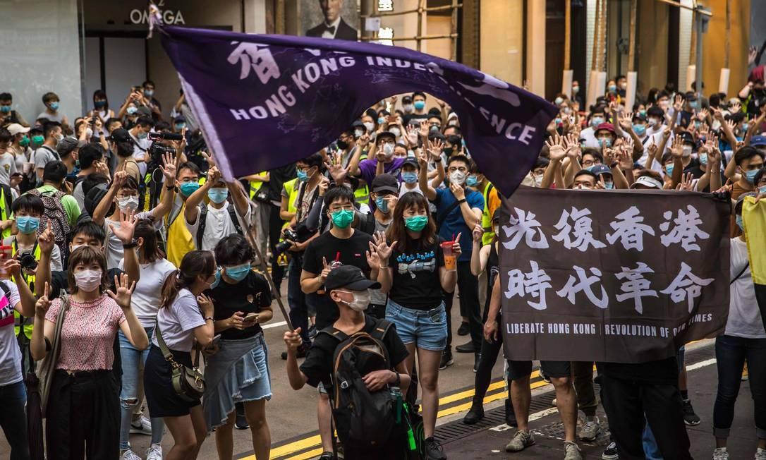 Manifestantes cantam slogans durante manifestação contra nova lei de segurança nacional Foto: DALE DE LA REY / AFP