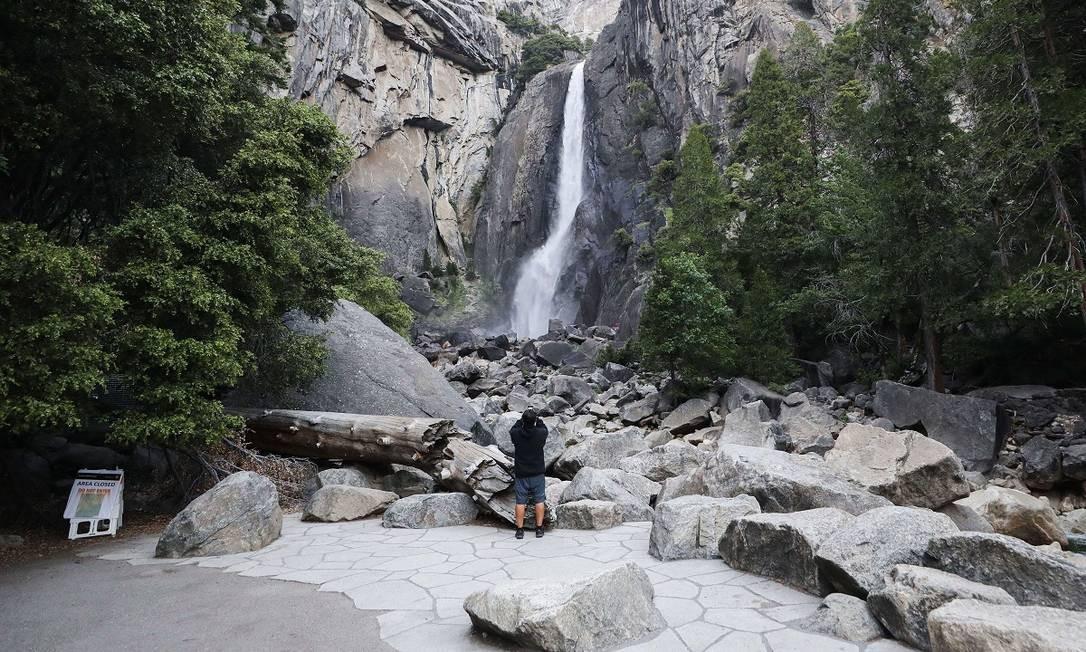Viajante solitário fotografa uma cachoeira no Yosemite National Park, na Califórnia Foto: Mario Tama / AFP