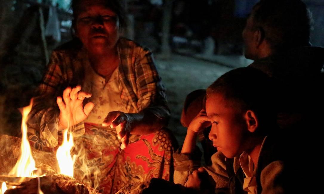 Uma mulher, cuja filha Mya Lay costumava trabalhar em uma mina de mármore, mas perdeu o emprego, senta-se junto a outros membros da família em sua casa em Sagyin, Mandalay, Mianmar Foto: ANN WANG / REUTERS