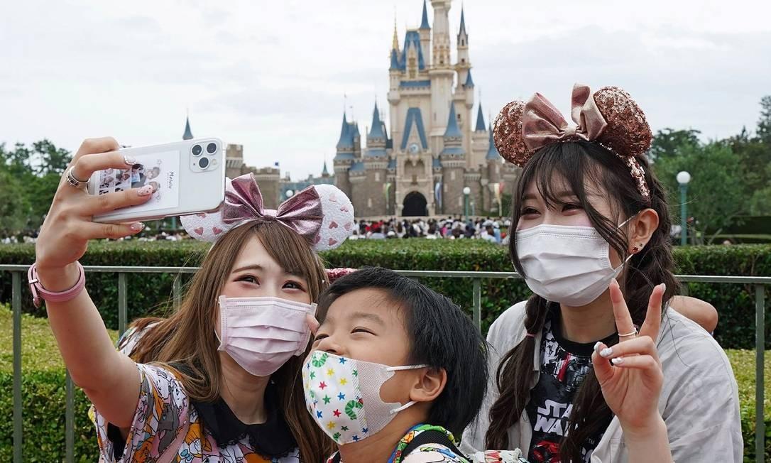 Visitantes posam para uma selfie em frente ao castelo da Disneyland de Tóquio, que reabriu em 1º de julho Foto: STR / AFP