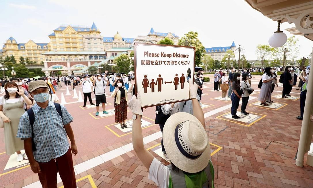 Funcionários da Disneyland de Tóquio orientam a entrada de visitantes, que, por sua vez, esperam em lugares pré-marcados, para evitar grandes aglomerações Foto: KYODO / REUTERS