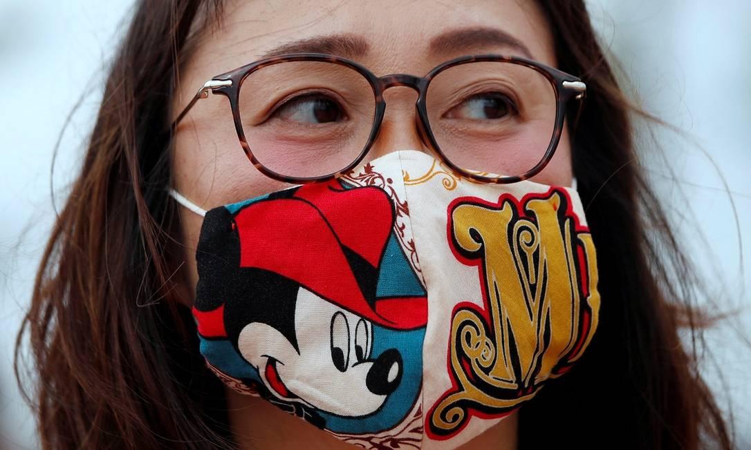 Visitante usa uma máscara com desenho do Mickey na reabertura da Disneyland de Tóquio Foto: ISSEI KATO / REUTERS