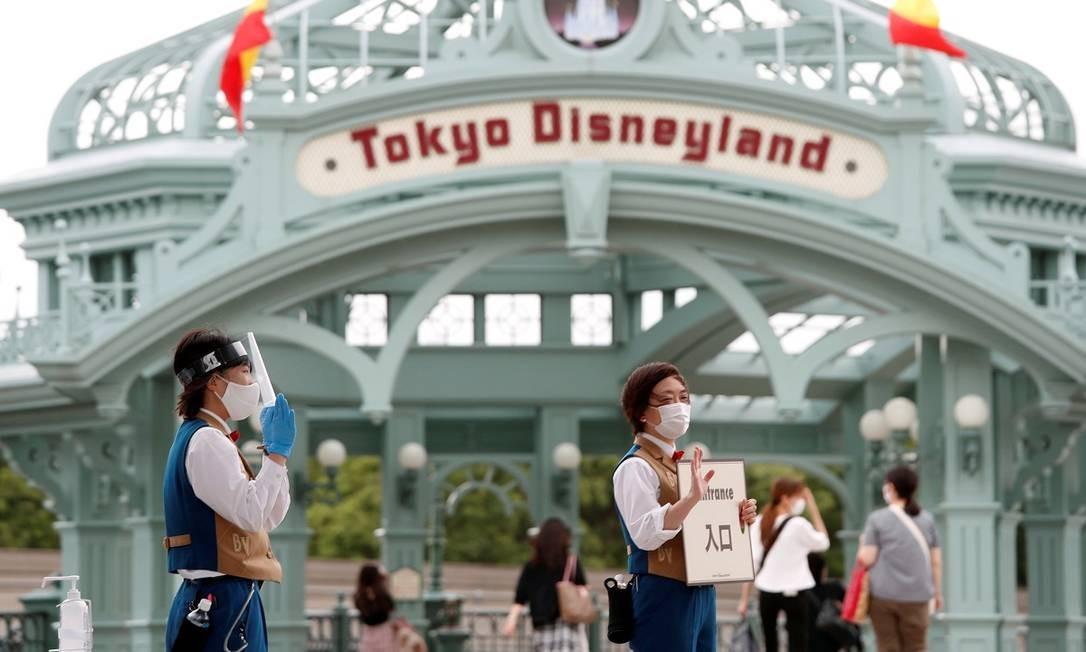 Funcionários da Tokyo Disneyland usando máscaras e outros equipamentos de proteção individual numa das entradas do parque Foto: ISSEI KATO / REUTERS
