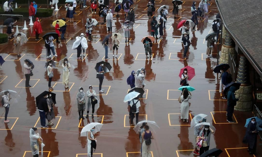 Nem a chuva desanimou os visitantes, que respeitaram o distanciamento estabelecido enquanto esperavam para entrar na Tokyo Disneyland Foto: ISSEI KATO / REUTERS