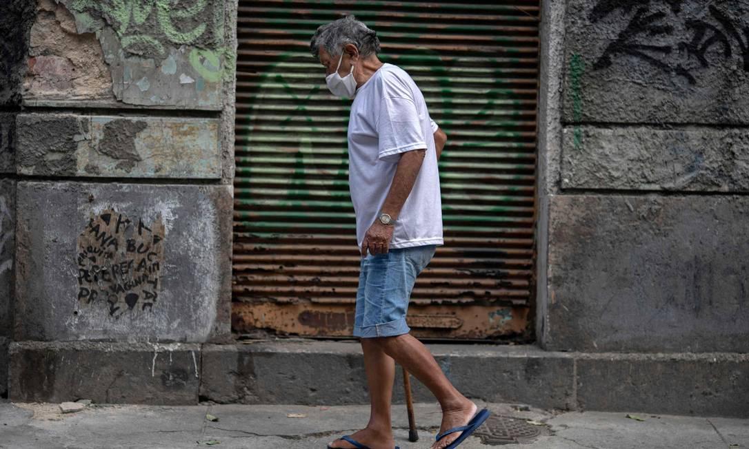 Senhor caminha de máscara no Centro do Rio nesta quinta-feira: dia da volta dos restaurantes na cidade Foto: Mauro Pimentel / AFP