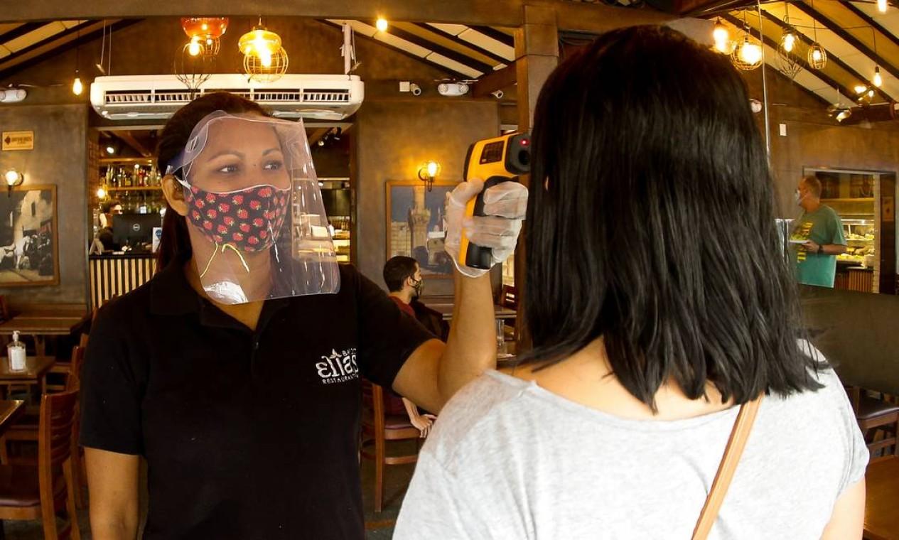 Cliente tem temperatura medida antes de entrar no Bar do Elias Foto: ROBERTO MOREYRA / Agência O Globo