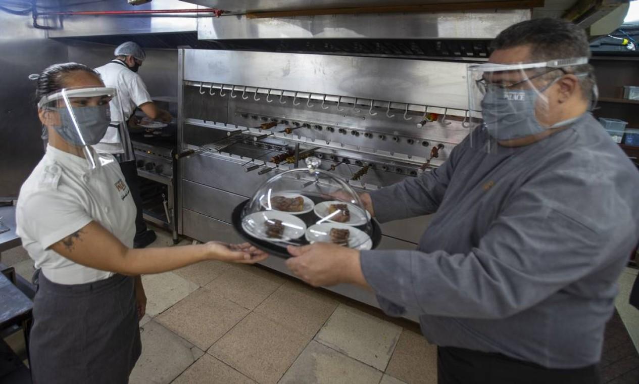 Funcionários utilizam máscara e face shield na cozinha da Churrascaria Palace. Pedidos são levados cobertos até a mesa dos clientes Foto: ANTONIO SCORZA / Agência O Globo