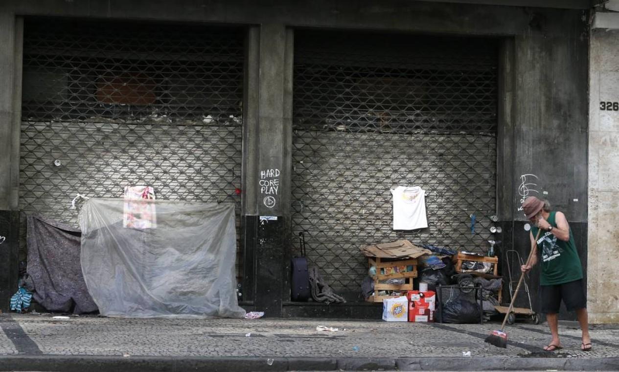 Homem varre calçada na Rua Graça Aranha, no Centro, onde tem alguns poucos pertences organizados em caixotes Foto: Pedro Teixeira / Agência O Globo