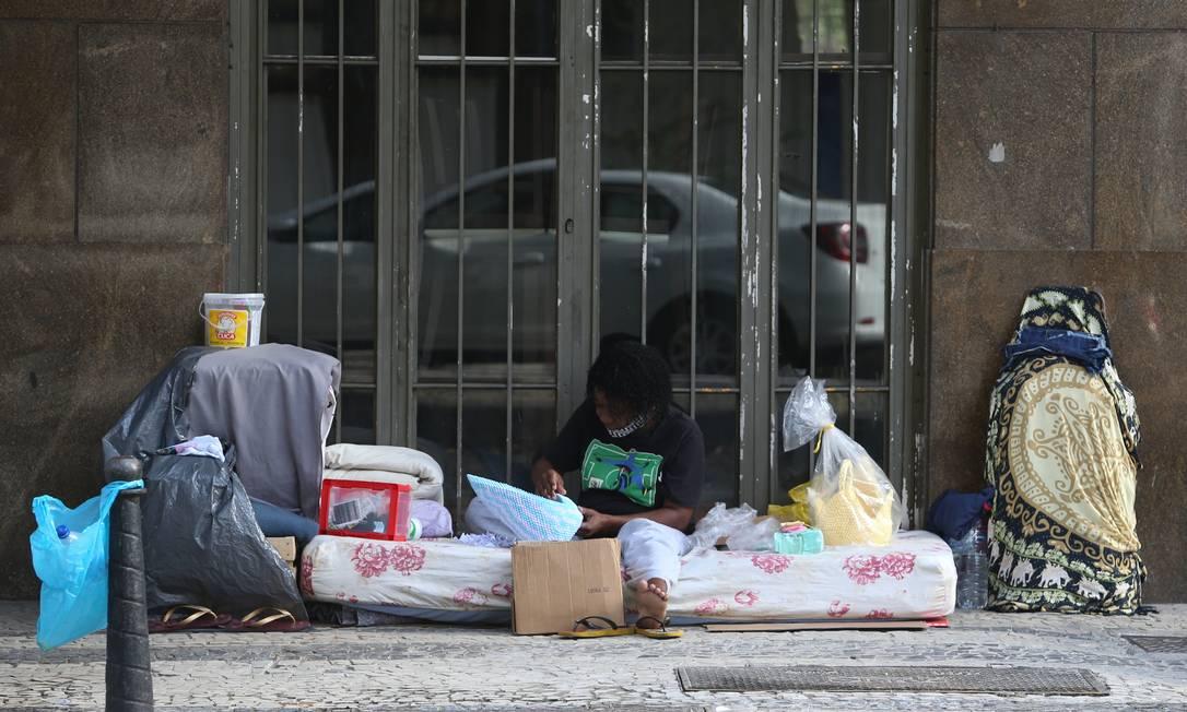 Uma mulher em situação de rua é vista com seus pertences na Rua Graça Aranha, no Centro Foto: Pedro Teixeira / Agência O Globo
