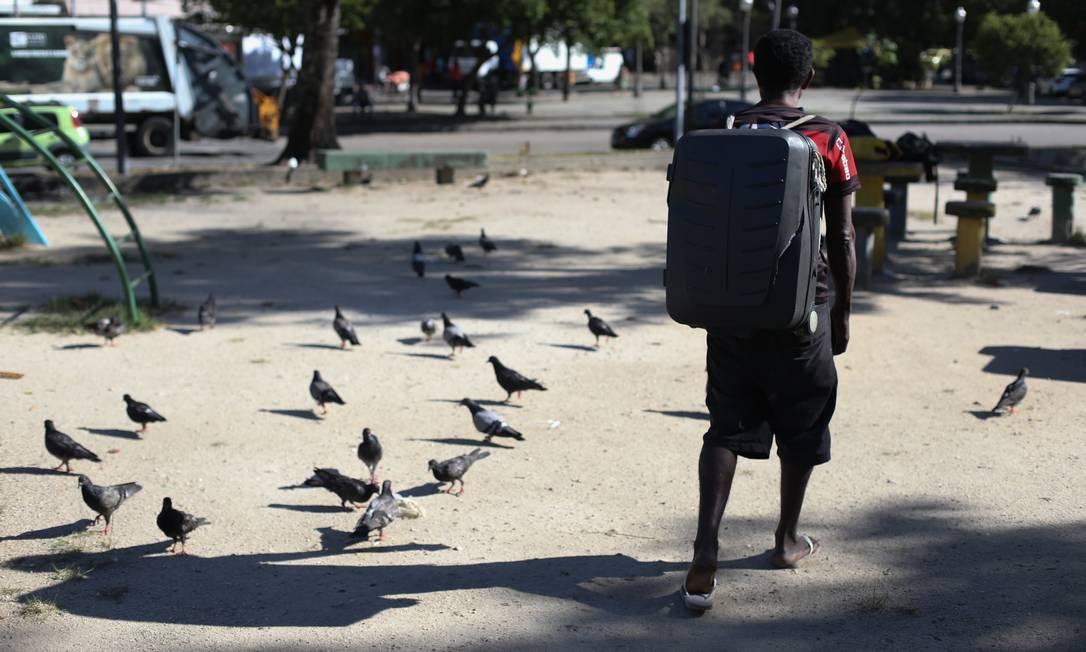 Com pertences guardados em uma mala de viagem, homem em situação de rua caminha por rua na Glória Foto: Pedro Teixeira / Agência O Globo