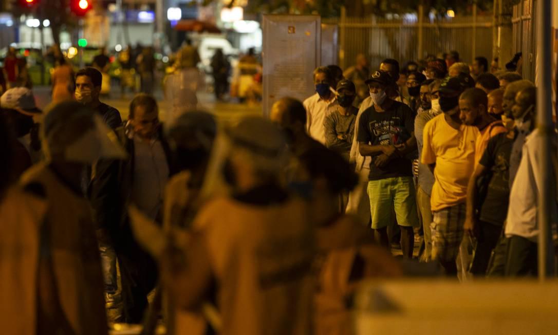 Pessoas em situação de rua aguardam em fila para refeição oferecida por equipe de freis franciscanos do Santuário e Convento de Santo Antônio, no Largo da Carioca Foto: Alexandre Cassiano / Agência O Globo