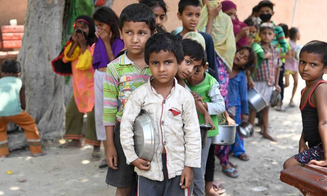 Crianças de uma favela em Nova Délhi, na Índia, fazem fila para receber comida: pandemia aprofundou as desigualdades sociais em todo o mundo Foto: PRAKASH SINGH / AFP