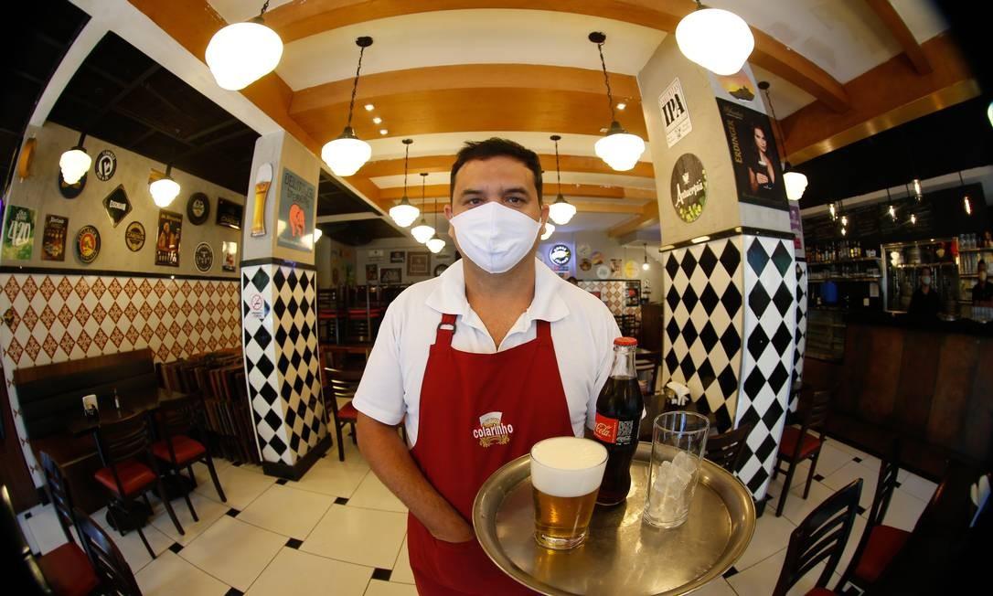 O garçom Marcos Bandeira usa a máscara enquanto entrega o pedido de um cliente, em um bar de Botafogo Foto: ROBERTO MOREYRA / O Globo