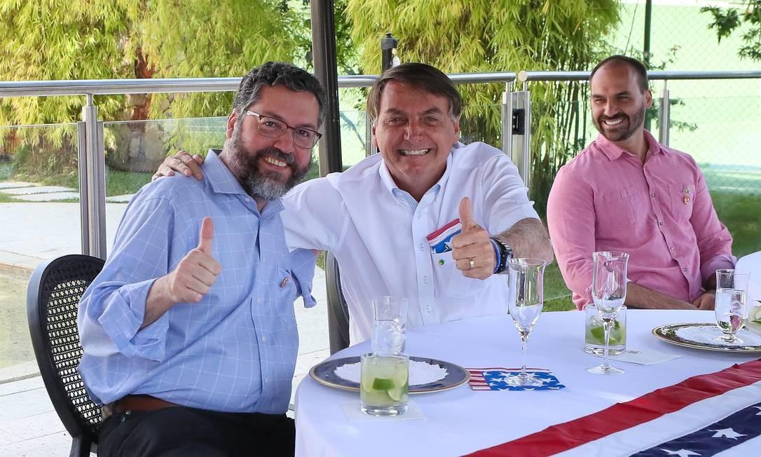 Presidente Bolsonaro abraça o ministro das Relações Exteriores, Ernesto Araújo, se abraçam à mesa, ao lado do deputado federal e filho, Eduardo Bolsonaro Foto: Divulgação / Divulgação