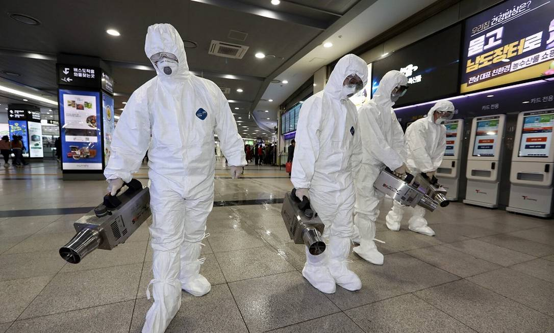 Trabalhadores da saúde desinfetam rodoviária: produtos aprovados eliminam vírus de superfícies não porosas. Foto: AFP