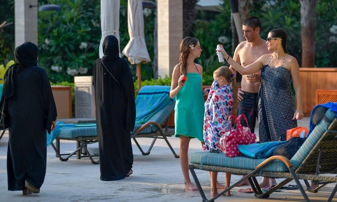 Hóspedes, vestindo roupas de banho ou trajes tradicionais, se encotram na piscina do Al Naseem, um dos hotéis de Dubai que reabriram as portas para os visitantes internacionais Foto: KARIM SAHIB / AFP