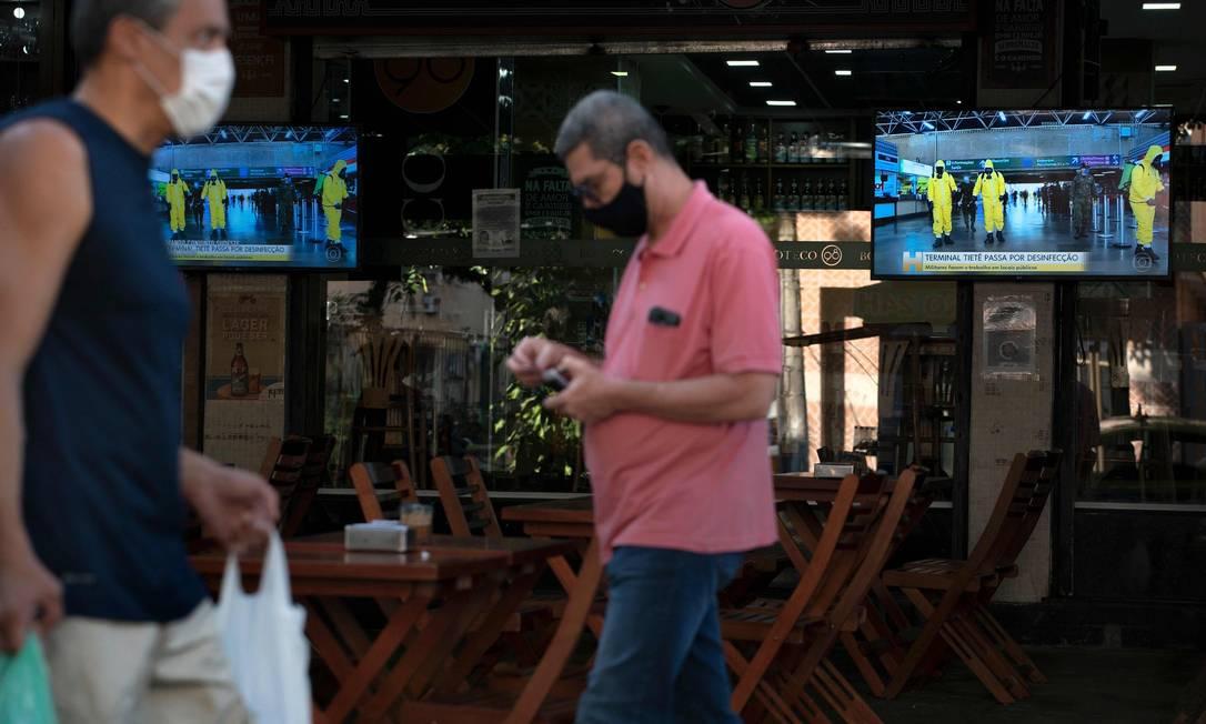 Pessoas caminham de máscara diante de restaurante em Botafogo, na Zona Sul do Rio, na última terça-feira (7) Foto: MAURO PIMENTEL / AFP