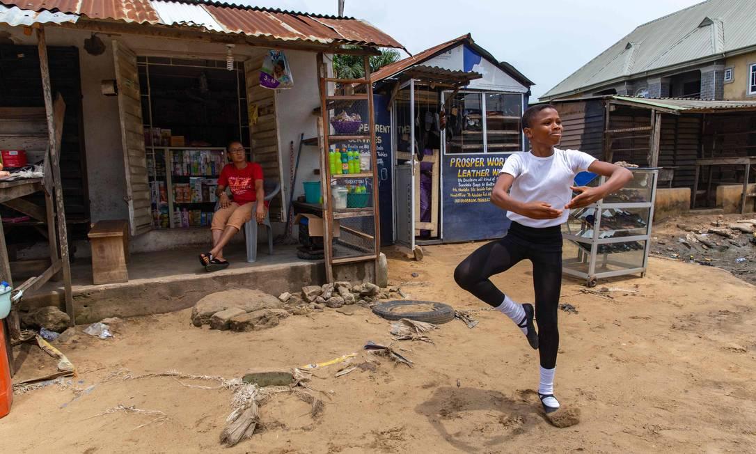 Um estudante da Academia Leap of Dance, Anthony Madu, realiza uma rotina de dança de balé em frente à loja de sua mãe na rua Okelola, na favela de Ajangbadi Foto: BENSON IBEABUCHI / AFP