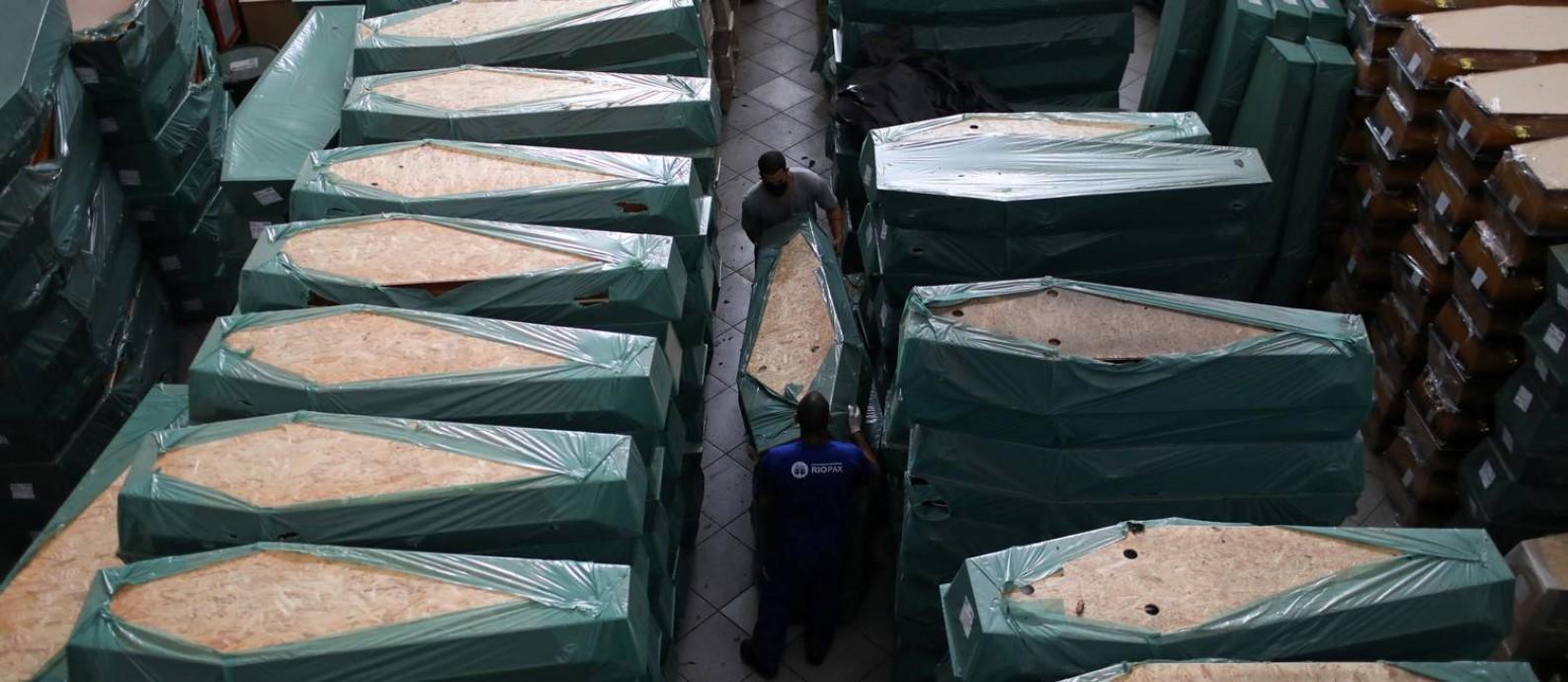 Funcionários carregam caixões em depósito de funerária no Rio Foto: Pilar Olivares / Reuters