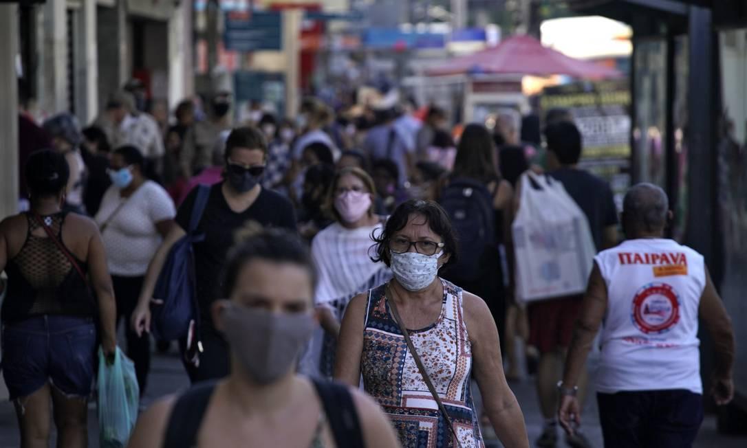 Pedestres caminham em meio a aglomerações na região da praça Saens Peña, na Tijuca, Zona Norte do Rio, na última quarta-feira (8) Foto: MAURO PIMENTEL / AFP
