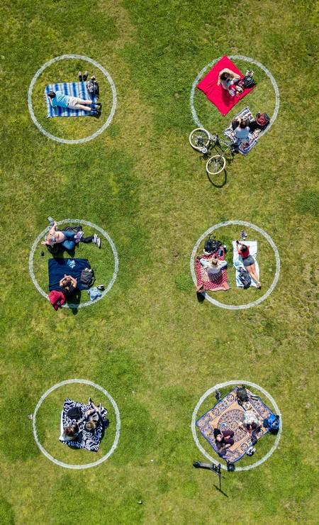 Pessoas reunidas dentro de círculos pintados na grama, incentivando o distanciamento social no Dolores Park, em São Francisco, Califórnia Foto: Josh Edelson / AFP