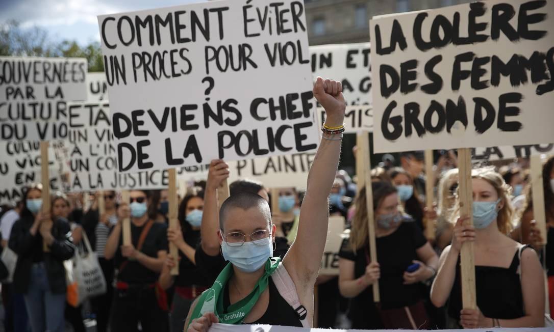 """""""Como evitar um julgamento de estupro? Tornando-se chefe de polícia"""", diz o cartaz atrás da mulher eu ergue o punho cerrado Foto: THOMAS COEX / AFP"""