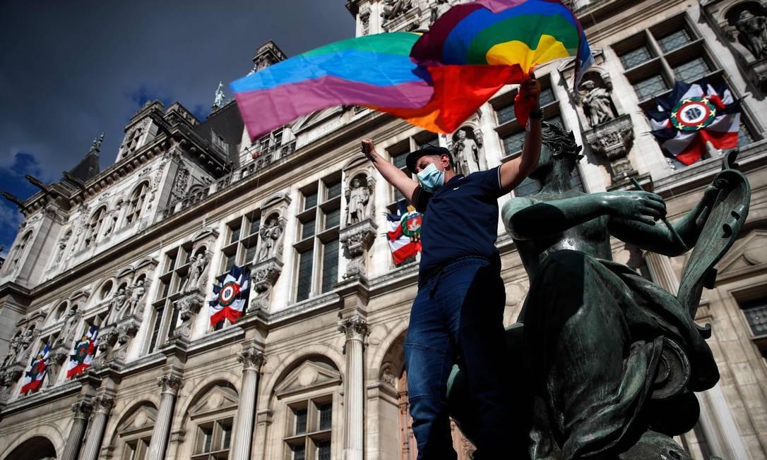 Manifestante agita uma bandeira do arco-íris, símbolo dos movimentos sociais LGBTQ+, durante uma manifestação convocada por movimentos feministas em frente à prefeitura de Paris Foto: THOMAS COEX / AFP
