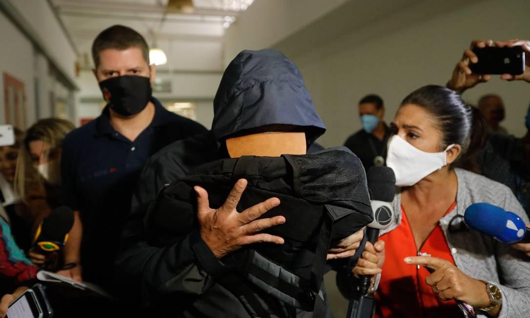 O ex-secretário de Saúde Edmar Santos esconde o rosto ao sair da Cidade da Polícia após depor Foto: Brenno Carvalho / Agência O Globo