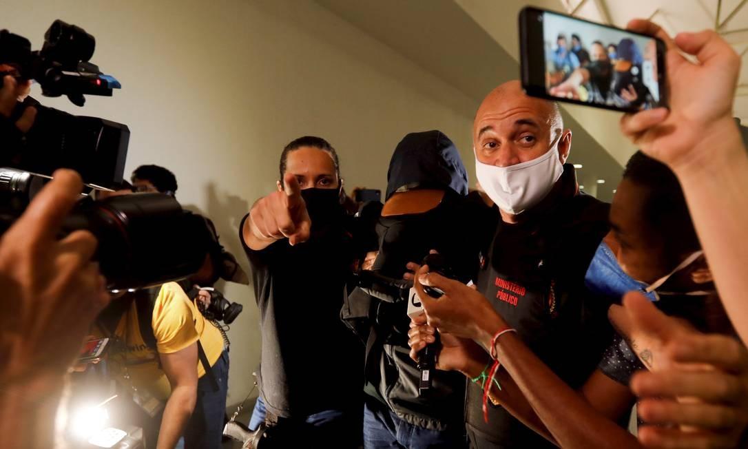 Investigado por compras superfaturadas durante a pandemia, o ex-secretário estadual de Saúde, o médico Edmar Santos, esconde o rosto ao chegar à Cidade da Polícia, no Jacarezinho Foto: Agência O Globo