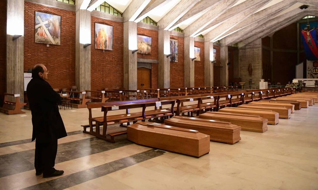Em março, padre da paróquia de Seriate, cidade próxima de Bergamo, abençoava caixões armazenados na igreja de São José Foto: PIERO CRUCIATTI / AFP / 26-03-2020