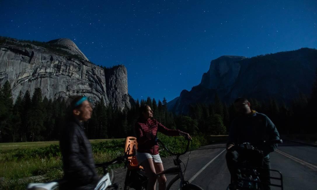 Três amigos observam as estrelas e o luar no vale de Yosemite, no Parque Nacional de Yosemite Foto: APU GOMES / AFP