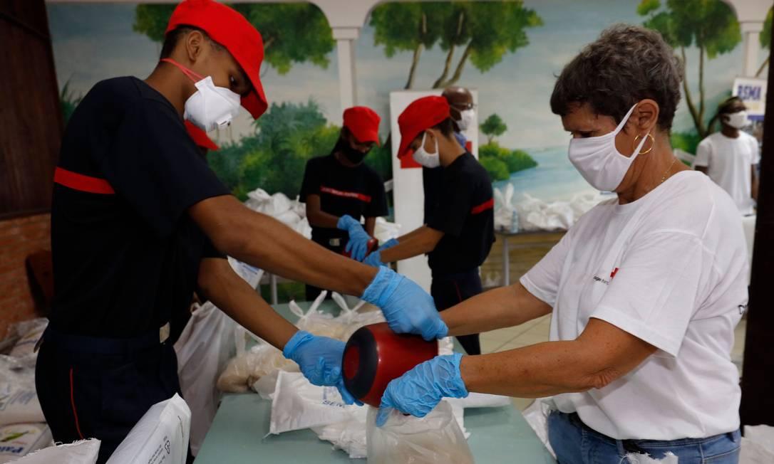 Voluntários preparam cesta básica para ser entregue na Guiana Foto: JODY AMIET / AFP