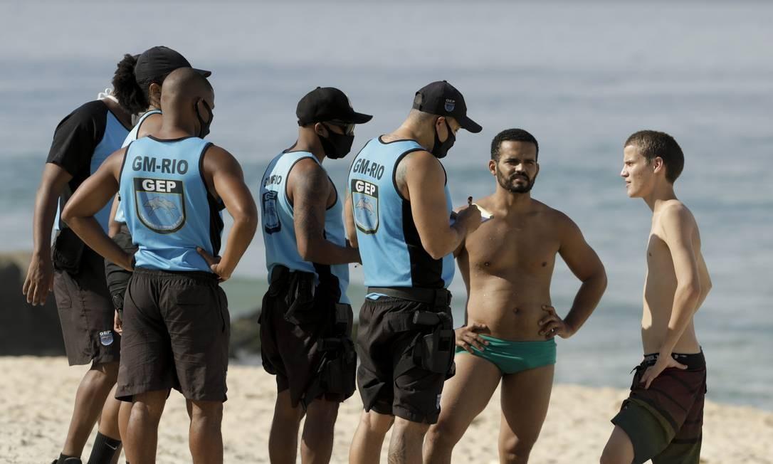 Dois jovens são multados por não usarem máscara na praia do Leblon, Zona Sul do Rio Foto: Gabriel de Paiva / Agência O Globo