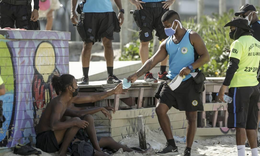 Máscaras eram distribuídas para quem estivesse sem o acessório na praia Foto: Gabriel de Paiva / Agência O Globo