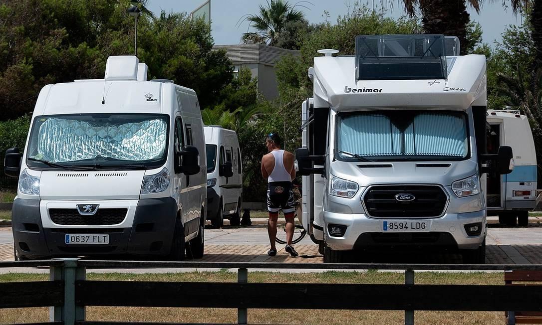 Um homem entre motorhomes num estacionamento público em Castellon, na Espanha Foto: Jose Jordan / AFP
