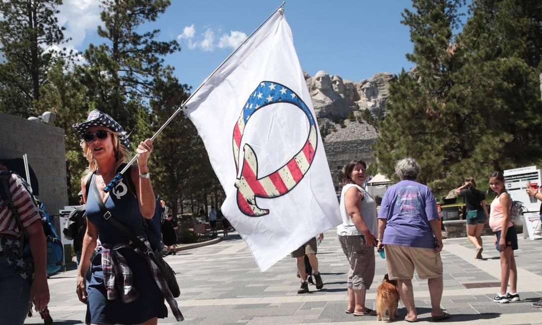 Apoiadora de Donald Trump carrega bandeira fazendo referência a QAnon em Keystone, nos EUA Foto: SCOTT OLSON / AFP