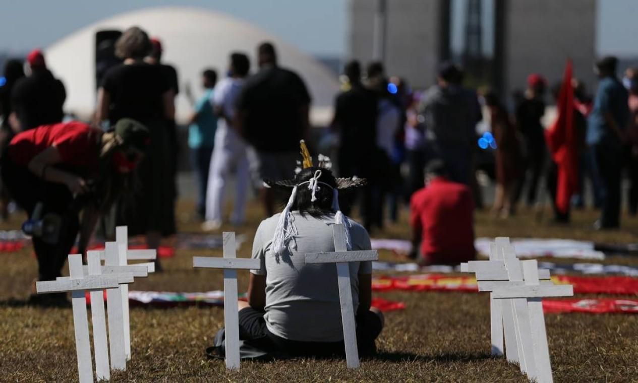Manifestante homenagearam as mais de 70 mil pessoas mortas durante a pandemia, com cruzes no gramado Foto: Jorge William / Agência O Globo