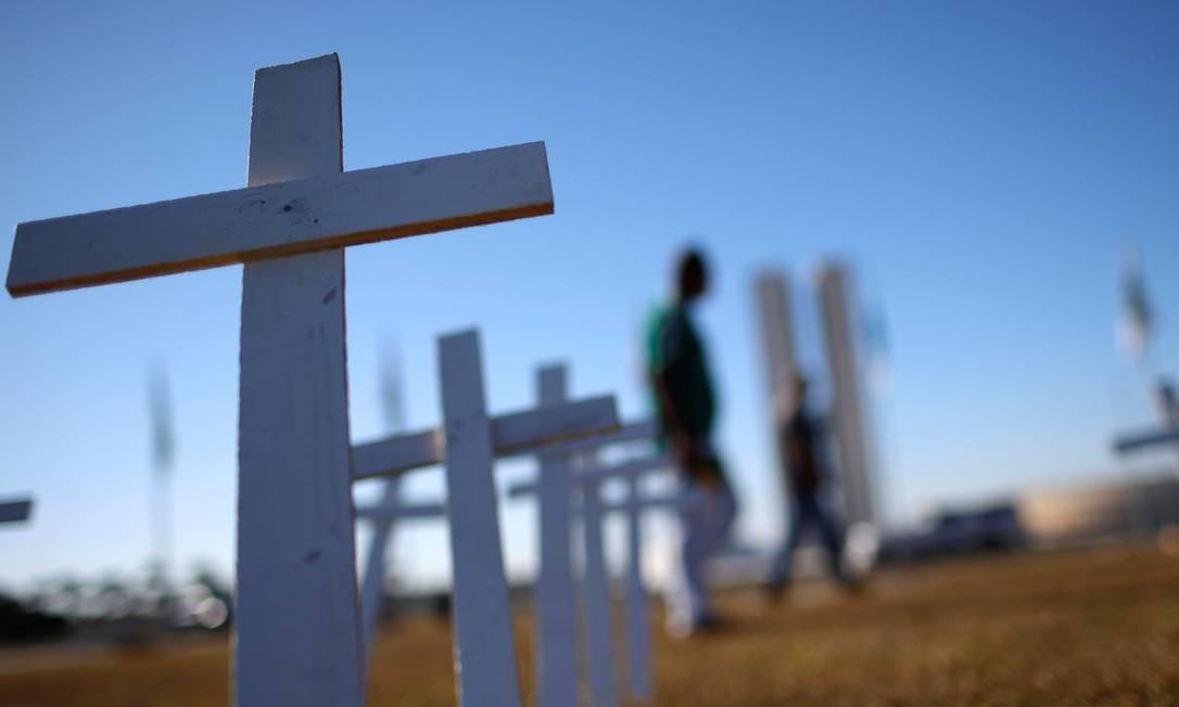 Cruzes foram fincadas no gramado do Congresso nacional para simbolizar as vidas perdidas na pandemia da Covid-19 Foto: Adriano Machado / Reuters
