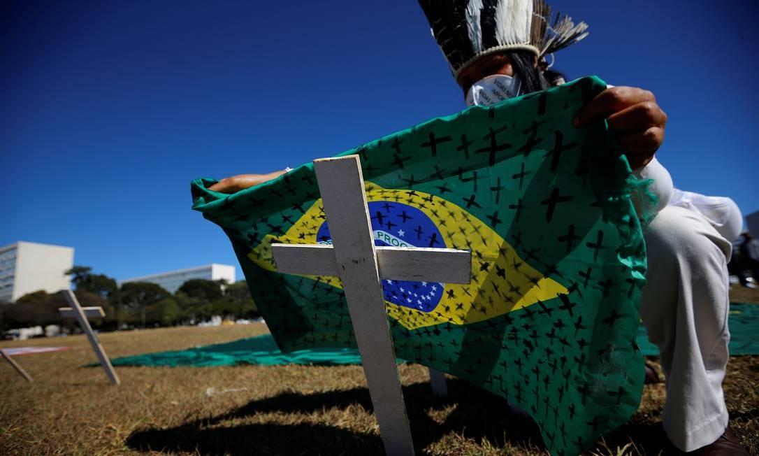 Ativista segura bandeira do Brasil com inúmeras cruzes pretas desenhadas em sinal de luto pelas vidas perdidas durante a pandemia Foto: Adriano Machado / Reuters