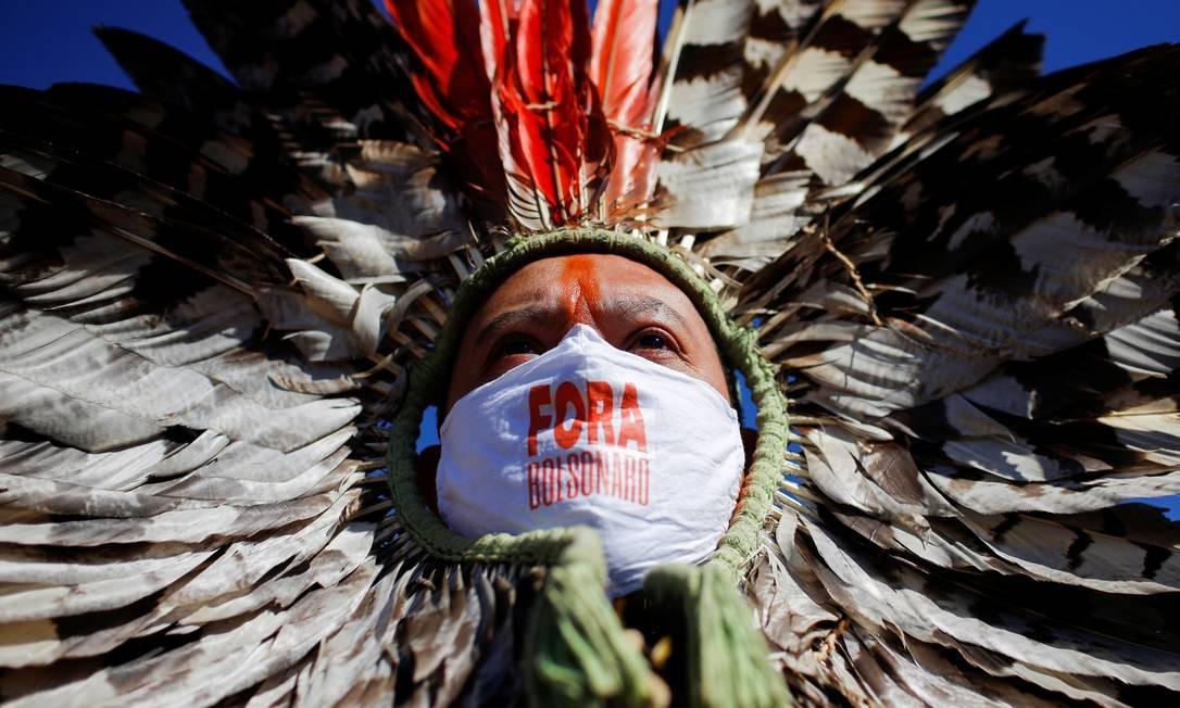 """O líder indígena Kretan Kaingang, da tribo Kaingang, usando uma máscara protetora com a frase """"Fora Bolsonaro"""", participa de um protesto contra o presidente do Brasil, Jair Bolsonaro, em frente ao Congresso Nacional, em Brasília Foto: Adriano Machado / Reuters"""