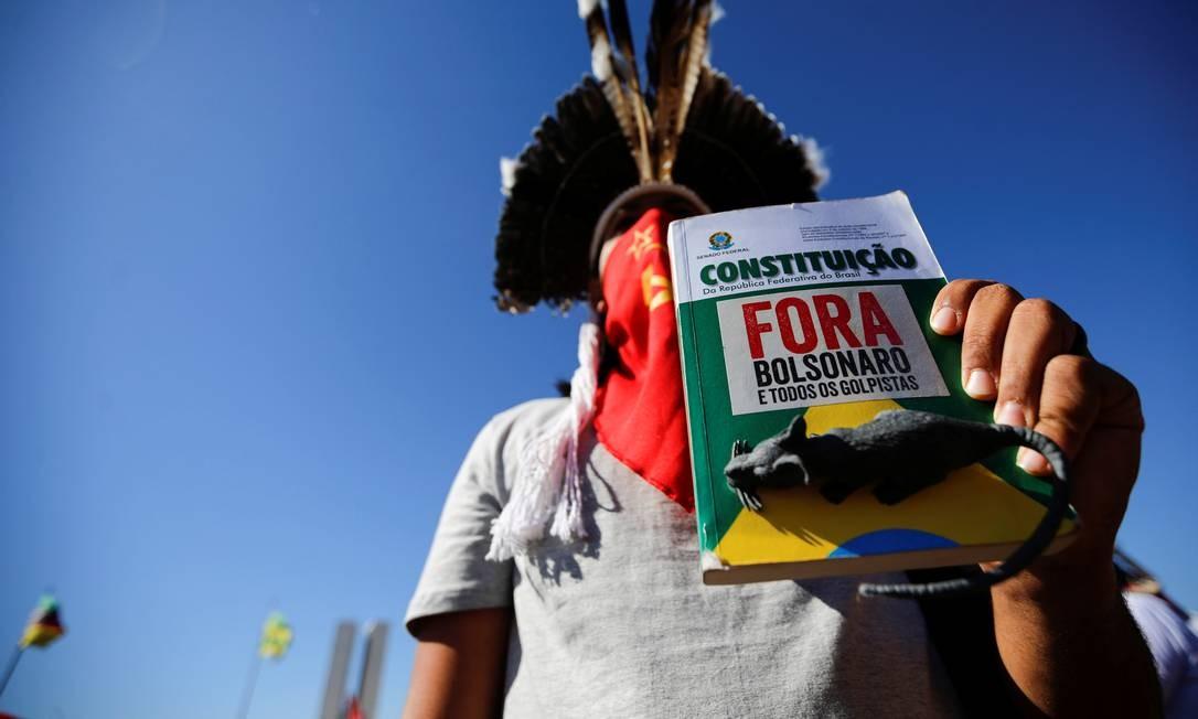 """Manifestante usando cocar indígena segura a Constituição com a mensagem """"Fora, Bolsonaro"""", e um rato de brinquedo colado Foto: Adriano Machado / Reuters"""