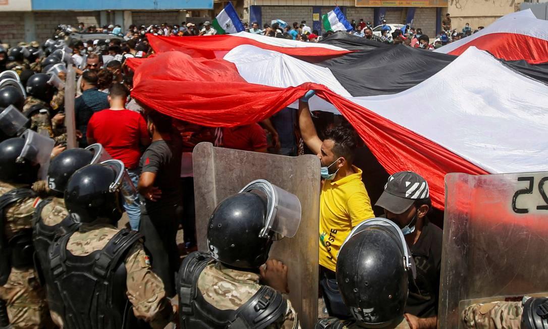 Forças de segurança iraquianas estão na frente de manifestantes em protestos contra o governo durante a visita do primeiro-ministro iraquiano, Mustafa al-Kadhimi, em Basra, Iraque Foto: ESSAM AL-SUDANI / REUTERS