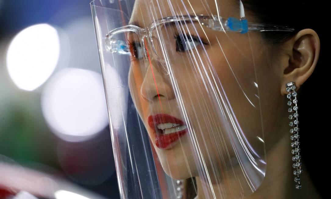 Um promotor usa um escudo facial durante o 41º Salão Internacional do Automóvel de Bangcoc, depois que o governo tailandês flexibilizou medidas restritivas de combate ao coronavírus, em Bangcoc, Tailândia Foto: JORGE SILVA / REUTERS