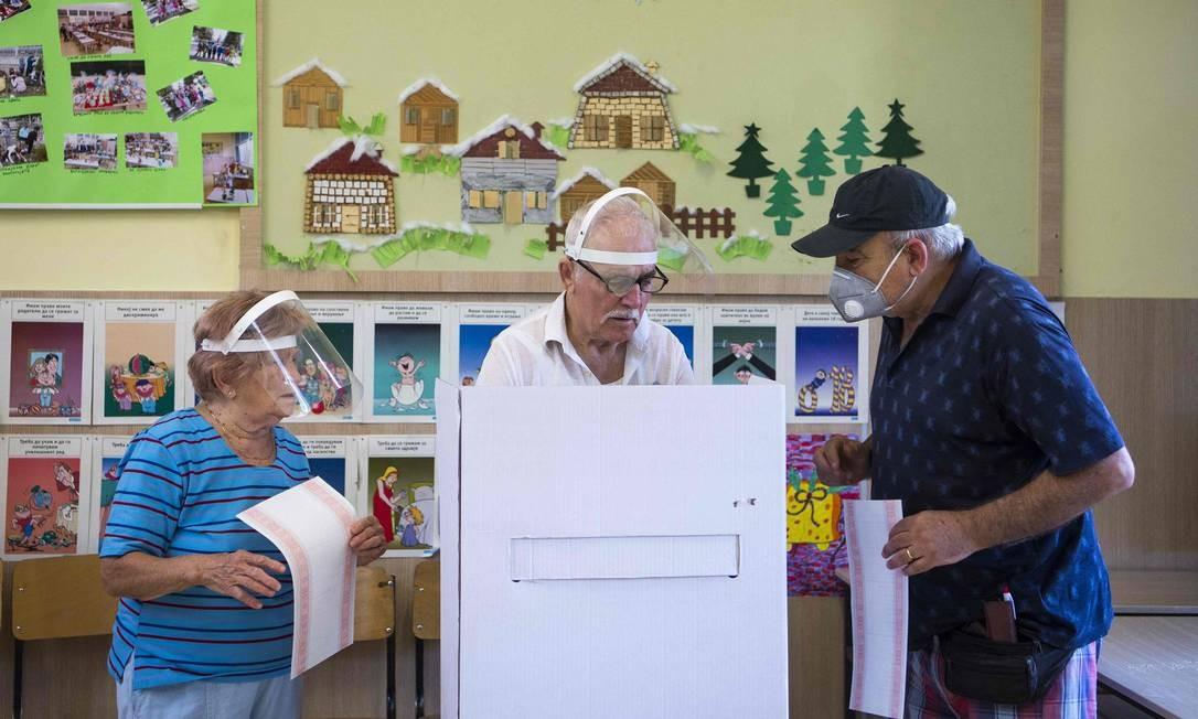 """Pessoas que usam equipamentos de proteção facial votam, durante as eleições gerais em Skopje. Macedônia do Norte foi às urnas em uma eleição parlamentar apertada. Os vencedores terão pela frente uma pandemia em ascenção e o início das negociações para aderir à União Europeia. É a primeira eleição parlamentar desde que o país dos Balcãs acrescentou """"Norte"""" a seu nome no início do ano passado, encerrando uma disputa de décadas com a Grécia Foto: ROBERT ATANASOVSKI / AFP"""