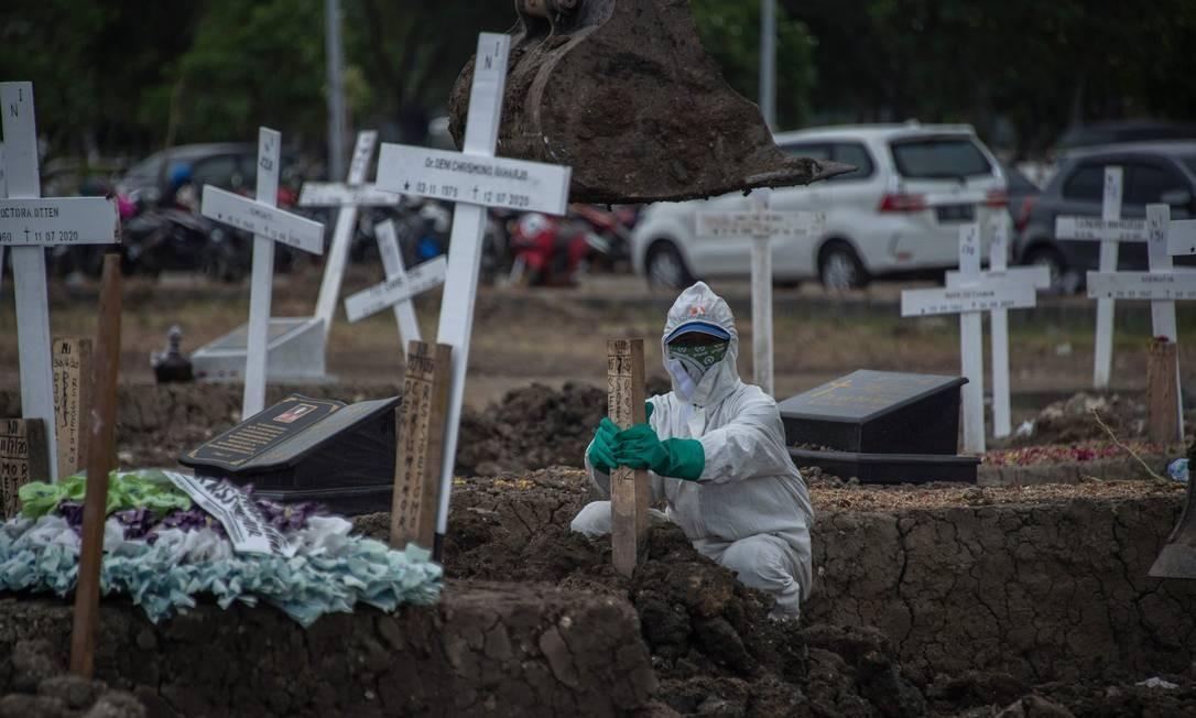 Trabalhador coloca lápides de madeira em um cemitério para vítimas do coronavírus, no cemitério Keputih, em Surabaya, Java Oriental, na Indonésia Foto: JUNI KRISWANTO / AFP