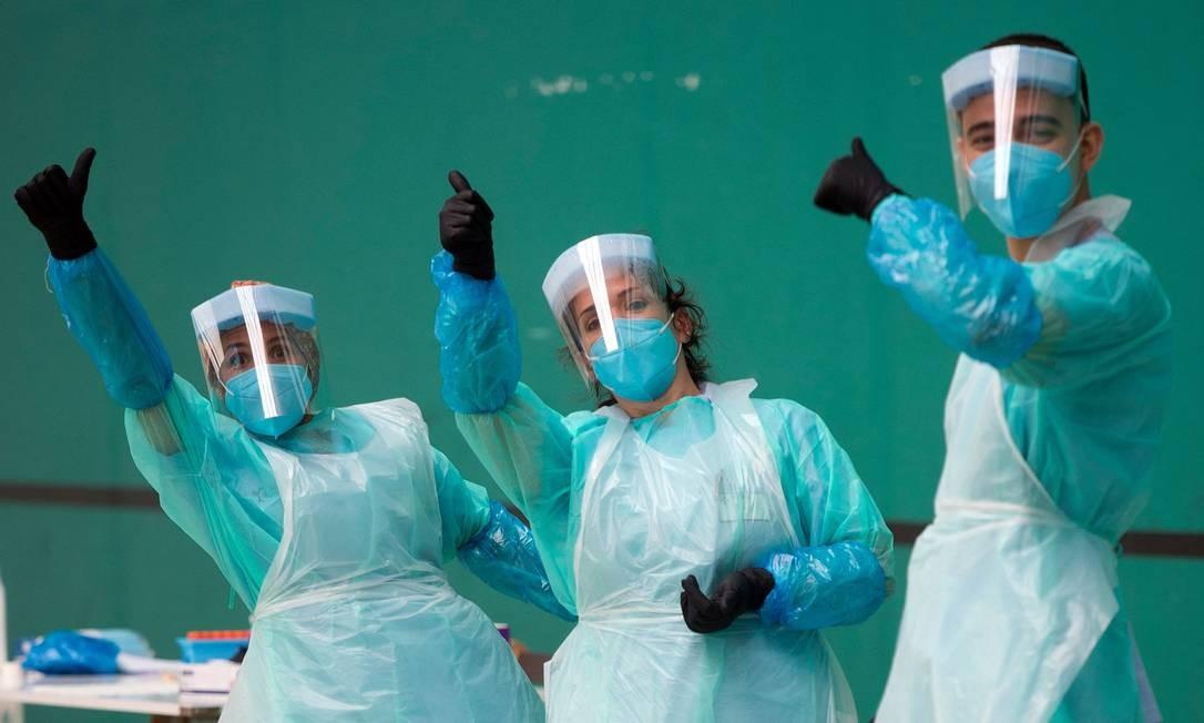 Profissionais de saúde prestam um polegar para cima em um centro de testes temporário para o novo coronavírus na cidade espanhola de Getaria Foto: ANDER GILLENEA / AFP