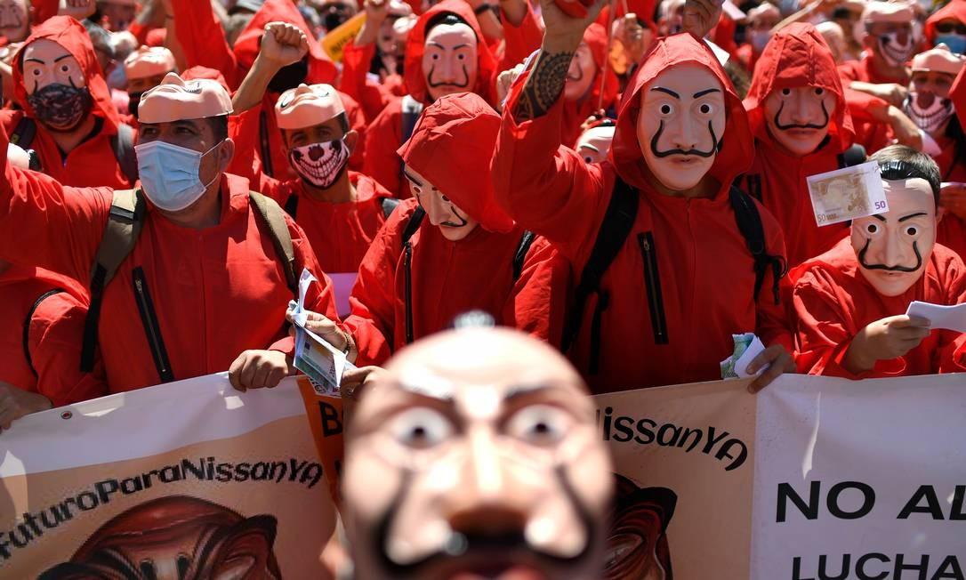Funcionários da Nissan, vestindo o macacão vermelho e a máscara Dali, da série espanhola La Casa de Papel, protestam em Madri, contra o fechamento da fábrica da montadora japonesa de Barcelona, que funcionava há 40 anos e deixou 3 mil desempregados Foto: GABRIEL BOUYS / AFP